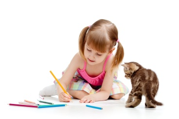 Cute girl drawing a picture with color pencils. Kitten looking a